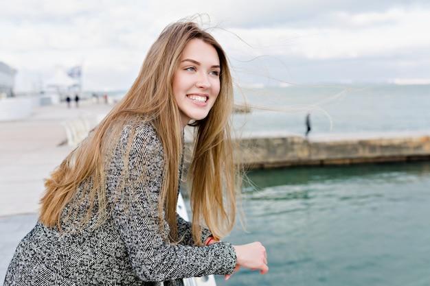 Gelukkige mooie vrouw met lang lichtbruin haar en grote blauwe ogen die lacht en in de buurt van de zee loopt