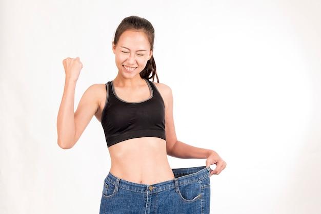 Gelukkige mooie vrouw verloren gewicht aan slanke vorm met grote jeans op witte achtergrond.