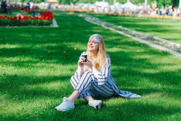 Gelukkige mooie vrouw zit op het groene gras in pyjama en slaapmasker en geniet van de zon en koffie drinken