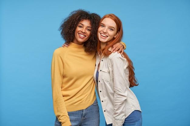 Gelukkige mooie vrouwen die in een leuke bui zijn en vrolijk glimlachen terwijl ze elkaar innig omhelzen, poseren voor de blauwe muur