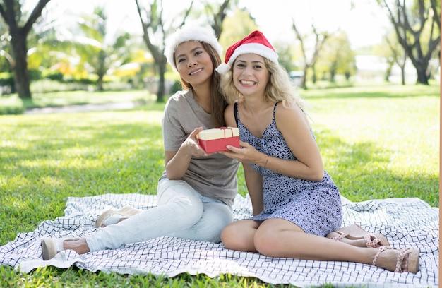Gelukkige mooie vrouwen die kerstmanhoeden dragen en giftdoos houden