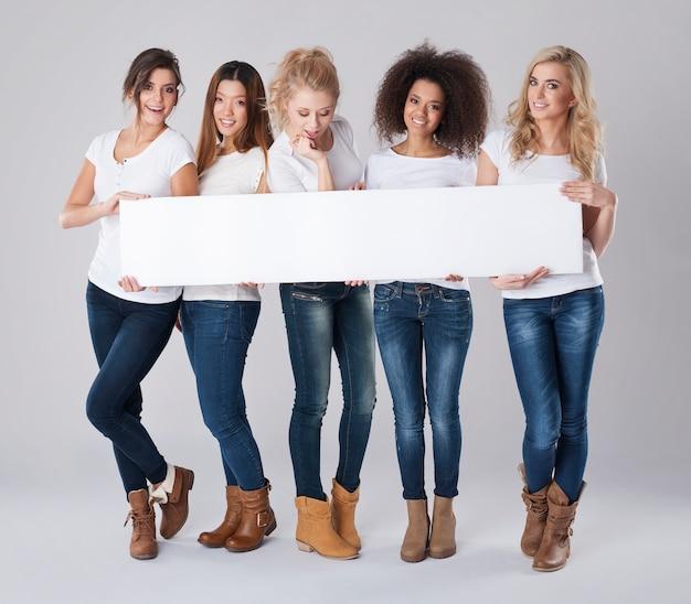 Gelukkige mooie vrouwen die leeg wit bord houden