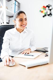 Gelukkige mooie zakenvrouw die laptop gebruikt voor werk terwijl ze op kantoor zit