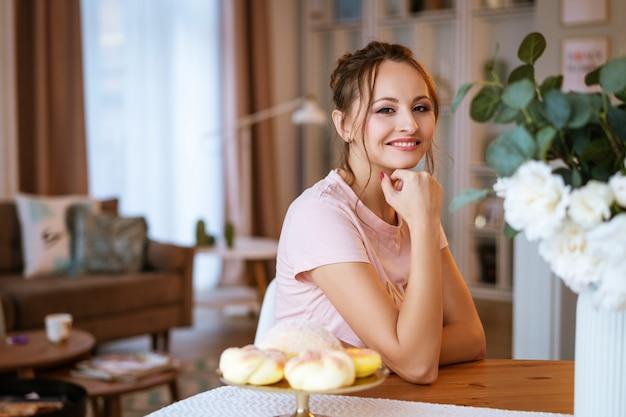 Gelukkige mooie zwangere vrouwenzitting bij de lijst en holding een cake