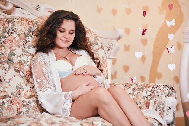 Gelukkige mooie zwangere vrouwenzitting op een bank in een kantjas en strelend haar buik