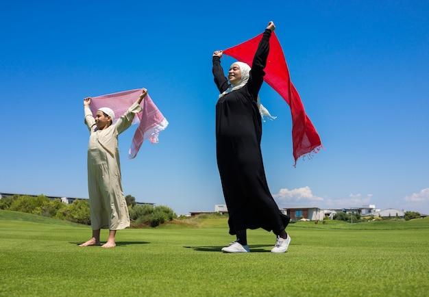 Gelukkige moslimfamilie op weide met sjaal
