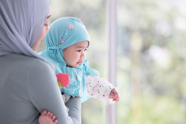Gelukkige moslimmoeder die een mooie kleine baby houdt