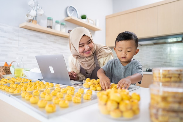 Gelukkige moslimmoeder die vanuit huis werkt en voedselbestelling maakt van nastar-ananascake voor eid mubarak kar