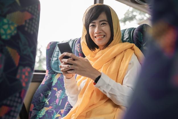 Gelukkige moslimvrouw die haar mobiele telefoon gebruikt terwijl zij een bus berijdt om terug naar huis te gaan