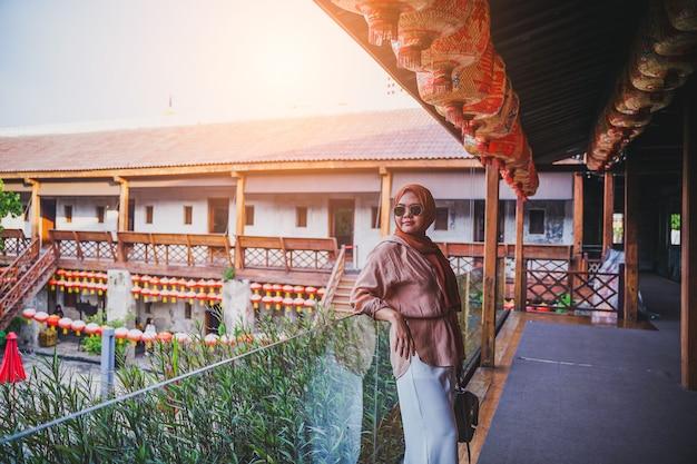 Gelukkige moslimvrouwentoerist die zich op mooie chinese huisatmosfeer bevinden, aziatische vrouw in vakantie. reizen concept. chinees thema.