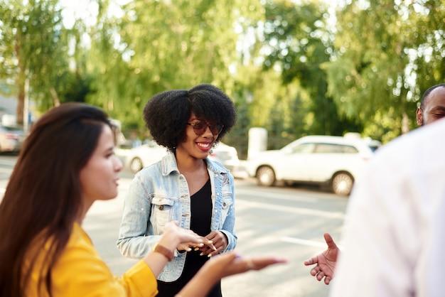 Gelukkige multi-etnische jongeren ontspannen samen, praten en praten met elkaar en delen ideeën.