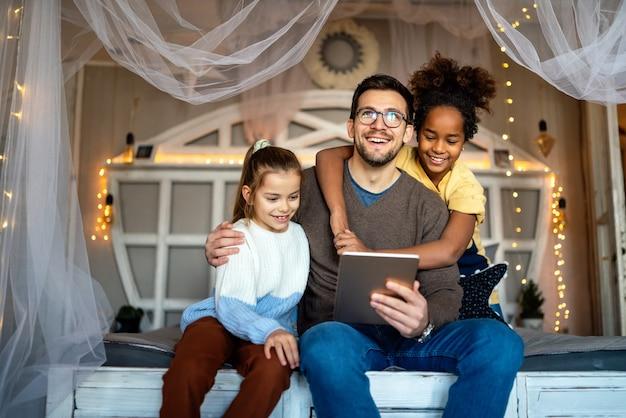 Gelukkige multi-etnische kinderen en vader die plezier hebben, thuis op tablet spelen