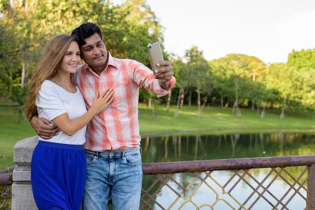 Gelukkige multi-etnische paar glimlachend en verliefd tijdens het nemen van selfie