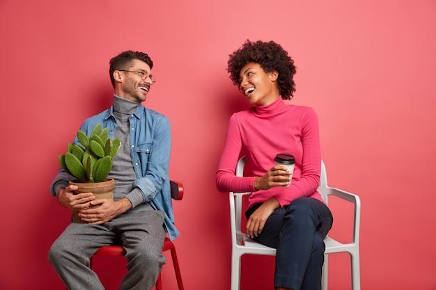 Gelukkige multi-etnische vrouw en man hebben een prettig gesprek, kijken elkaar aan en poseren op stoelen