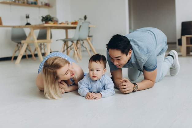 Gelukkige multiculturele familie plezier samen in de keuken. aziatische vader en blanke moeder leren zoon te kruipen