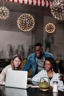 Gelukkige multiculturele vrienden die laptop bekijken