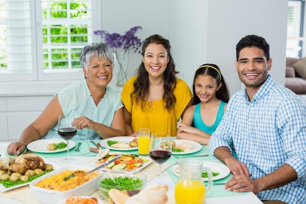 Gelukkige multigeneratiefamilie die maaltijd op lijst hebben thuis