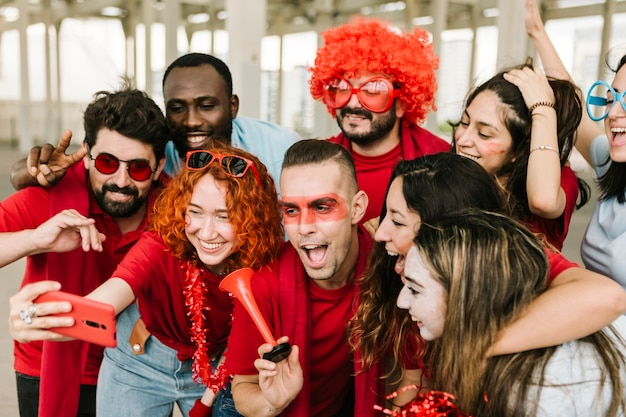 Gelukkige multiraciale groep voetbalfans die selfie maken met mobiele telefoon
