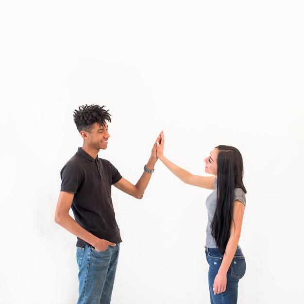 Gelukkige multiraciale mannelijke en vrouwelijke vrienden die hoogte vijf op witte achtergrond geven