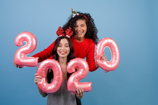 Gelukkige multiraciale meisjes met 2020 nieuwe jaarballons en grappige vakantiehoepels die over blauw worden geïsoleerd