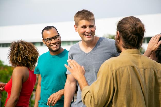 Gelukkige multiraciale mensen praten buitenshuis