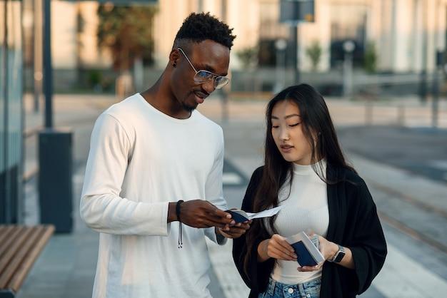 Gelukkige multiraciale paar kijken instapkaart vertrektijd controleren bij de halte in de buurt van de luchthaven. vakantiereis concept.
