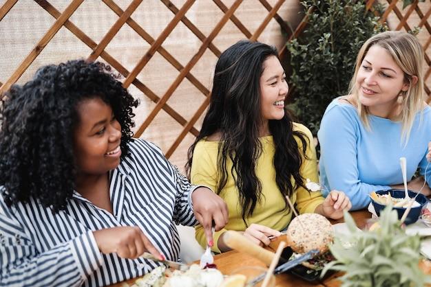 Gelukkige multiraciale vrienden die buiten ontbijten in het terrasrestaurant - hoofdfocus op het gezicht van een aziatisch meisje