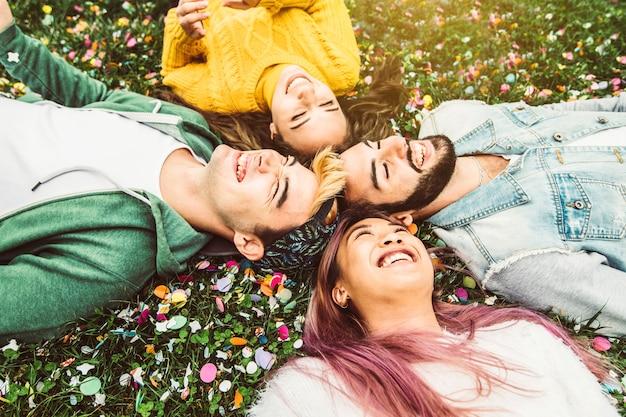 Gelukkige multiraciale vrienden die op het gras liggen die samen lachen