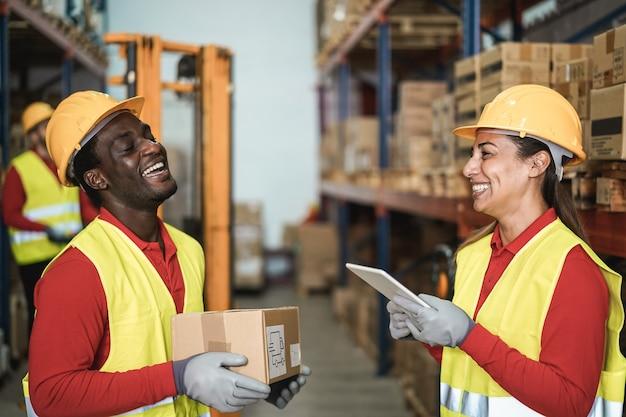 Gelukkige multiraciale werknemers die plezier hebben in het magazijn - focus op het gezicht van de vrouw