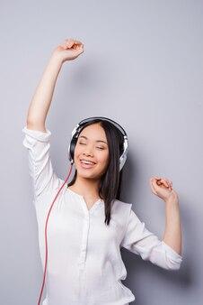 Gelukkige muziekliefhebber. mooie jonge aziaat in koptelefoon met ogen gesloten en armen omhoog terwijl ze tegen een grijze achtergrond staan