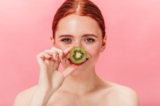 Gelukkige naakte vrouw die rijpe kiwi houdt en camera bekijkt. studio shot van gember europees meisje met fruit geïsoleerd op roze achtergrond.