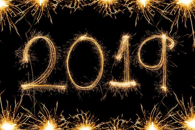 Gelukkige nieuwe jaar 2018 tekst die met fonkelingsvuurwerk wordt geschreven dat op zwarte achtergrond wordt geïsoleerd