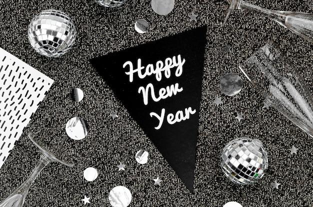 Gelukkige nieuwe jaarslinger met zilveren toebehoren op donkere achtergrond