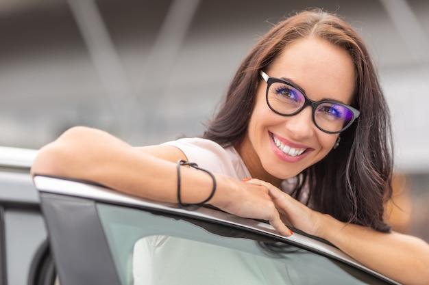 Gelukkige nieuwe vrouwelijke autobezitter leunt met een grote glimlach op de open deur van het voertuig.