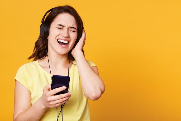 Gelukkige onbezorgde jonge vrouw die aan muziek van smartphone over studio luistert.