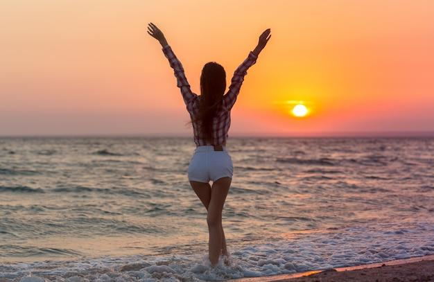 Gelukkige onbezorgde vrouw op het strand dat van de zomer geniet