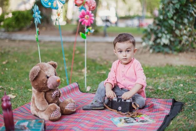 Gelukkige ondergeschikte babyjongen in de tuin op een zonnige dag