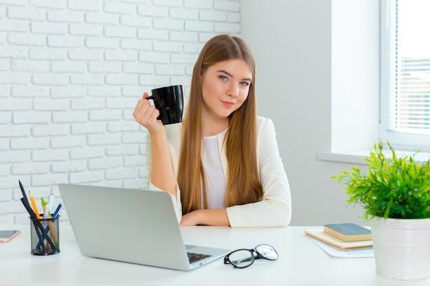 Gelukkige onderneemster die aan laptop op kantoor werkt