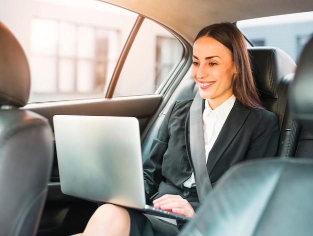 Gelukkige onderneemster die door auto reist die laptop met behulp van