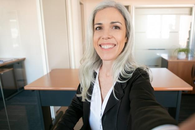 Gelukkige onderneemster die en camera glimlacht bekijkt. succesvolle zelfverzekerde grijsharige manager zit in kantoorruimte. werkplek-, bedrijfs- en managementconcept