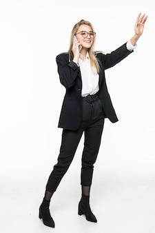 Gelukkige onderneemster die met smartphone iemand begroeten. mooie jonge vrouw die in formele slijtage mobiele telefoon houden en geïsoleerde hand golven. technologie concept