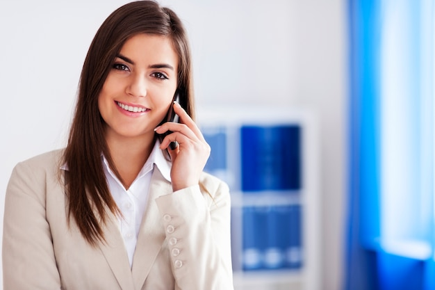 Gelukkige onderneemster die op mobiele telefoon spreekt