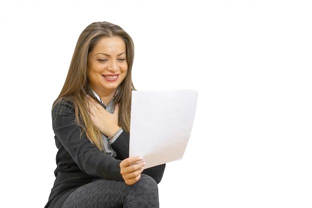 Gelukkige ondernemersvrouw die goed nieuws in een brief op bank leest