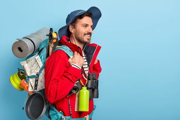 Gelukkige ongeschoren man leidt een actieve levensstijl, houdt van reizen en iets nieuws ontdekken, draagt een toeristenrugzak met een slaapdoek