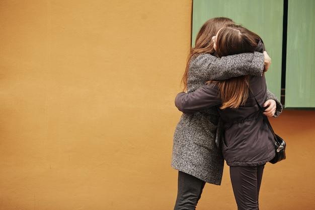 Gelukkige ontmoeting van twee vrienden knuffelen in de straat