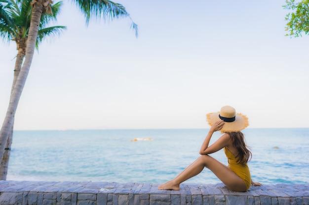 Gelukkige ontspannen de portret mooie jonge aziatische vrouwen glimlach rond overzeese strandoceaan