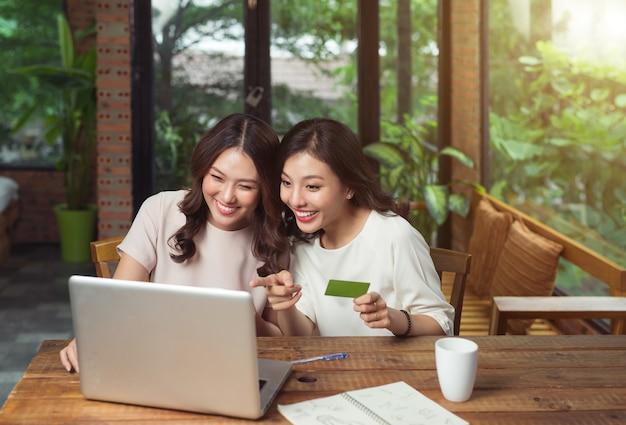 Gelukkige ontspannen jonge vrouwelijke vrienden die thuis online winkelen via laptop en creditcard