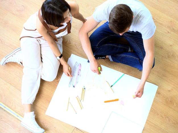 Gelukkige ontwerpers die aan een document werken met collega's die erachter werken