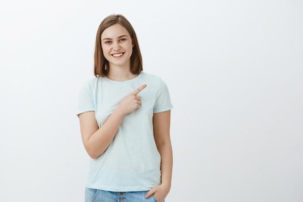 Gelukkige opgetogen en zorgeloze jonge vrouw die op copyspace richt