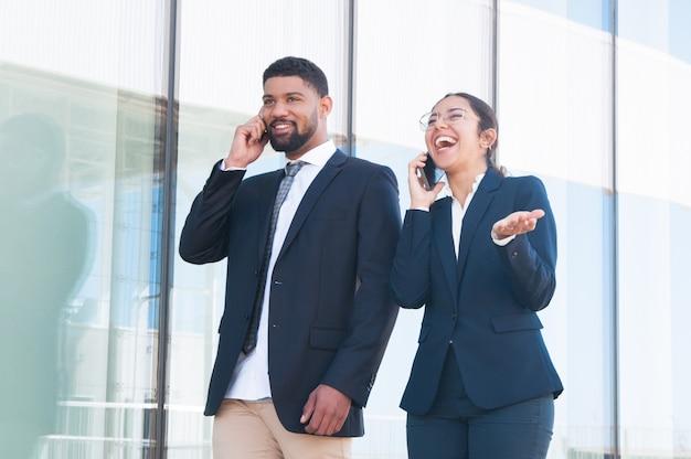 Gelukkige opgewekte bedrijfscollega's die van grappige telefoonbesprekingen genieten